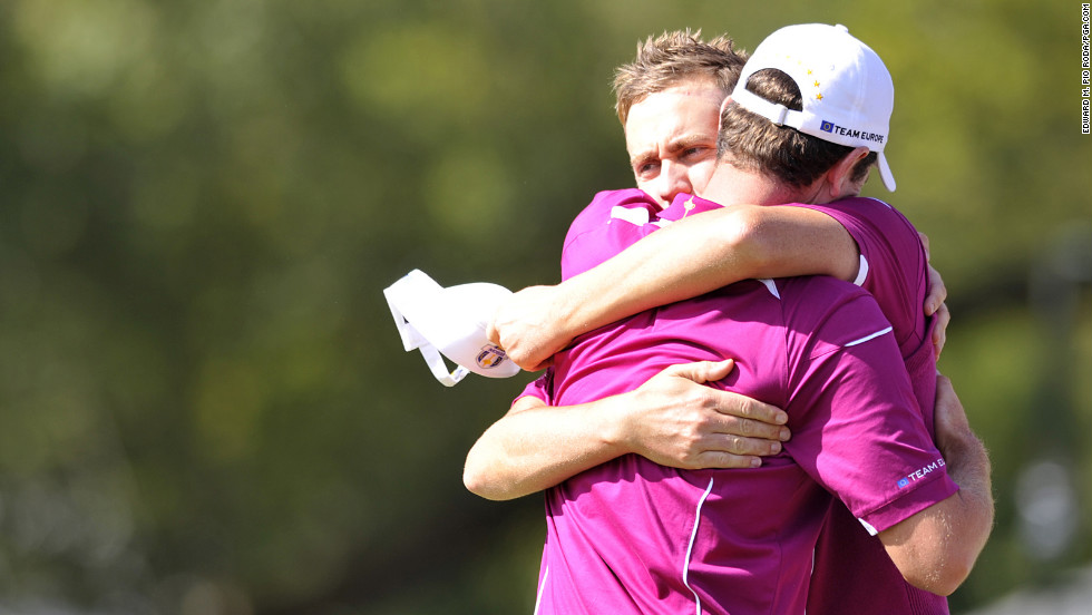 Poulter and Justin Rose of Team Europe embrace after winning their match on Saturday.