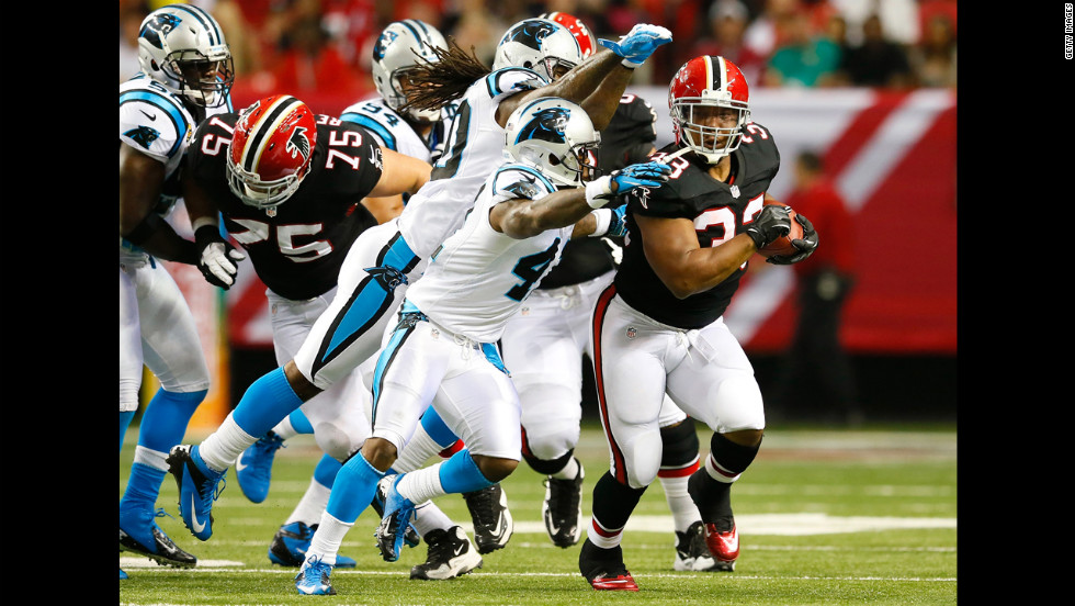 Michael Turner of the Atlanta Falcons rushes away from Carolina Panthers defenders on Sunday.