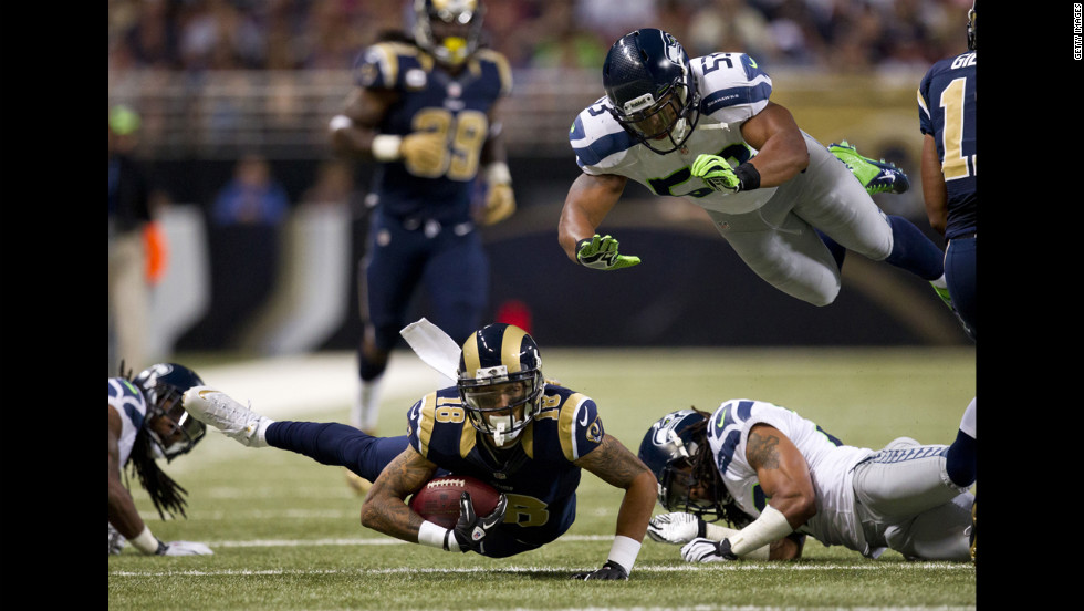Austin Pettis of the St. Louis Rams tries to stay upright with the ball as Malcolm Smith of the Seattle Seahawks attempts to make a diving tackle on Sunday.