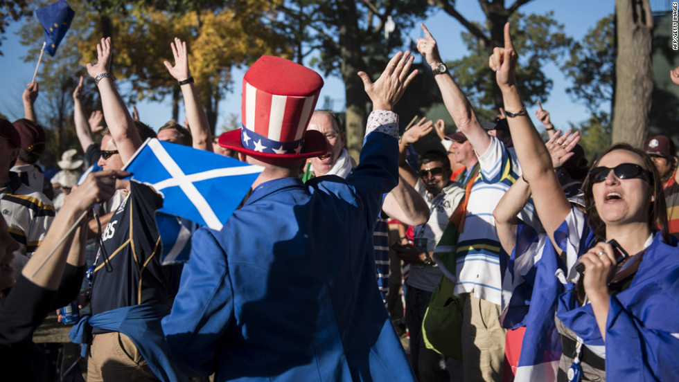 A U.S. fan high-fives Team Europe's fans after their Ryder Cup victory on Sunday.