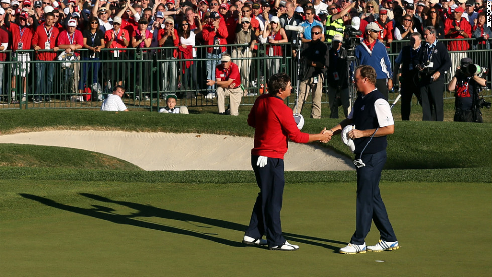 Jason Dufner of the United States, left, shakes hands with Peter Hanson on the 18th green after Dufner defeated Hanson.