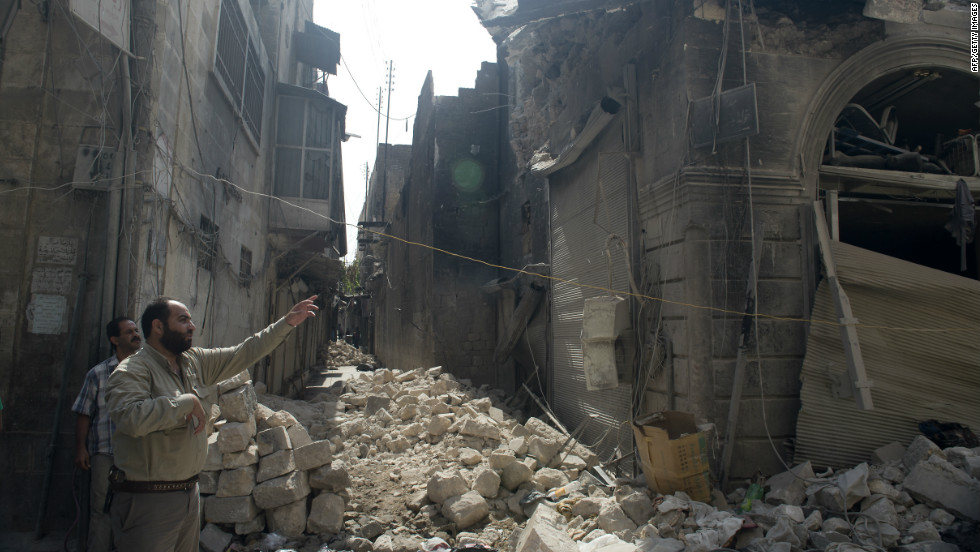 Syrians inspect damages in the old city of Aleppo after the area was shelled by Syrian regime forces on Sunday.