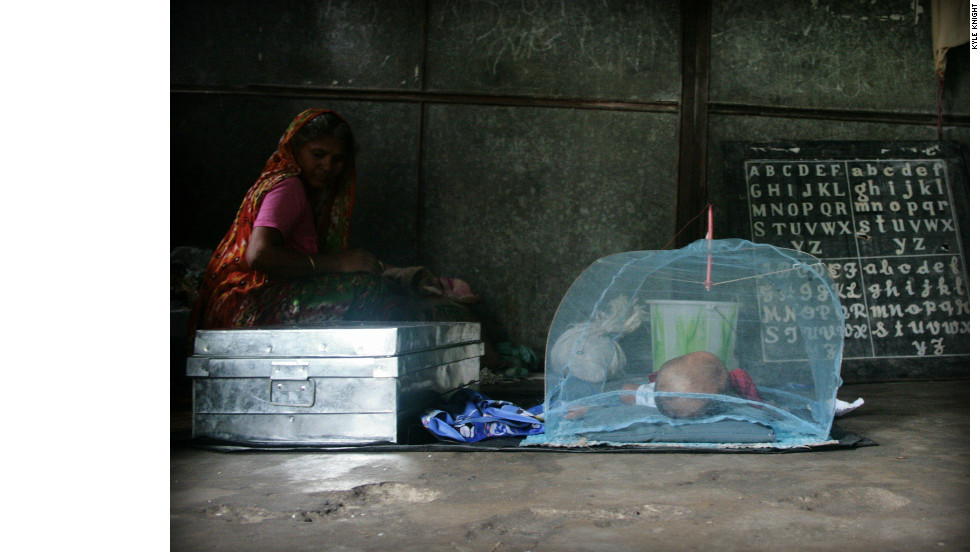 An infant sleeps in a classroom that has been converted into a dormitory.