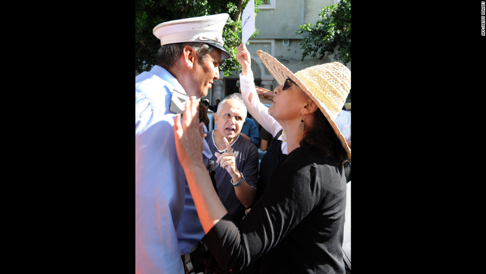 A Tunisian protester talks to a police officer during Tuesday's demonstration.
