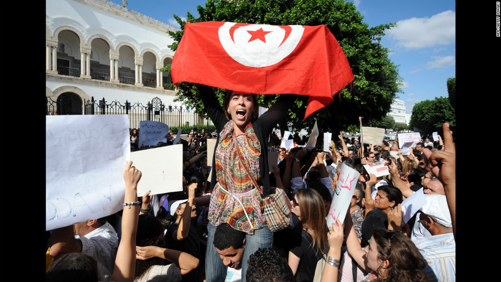 A Tunisian protester holds up a national flag.