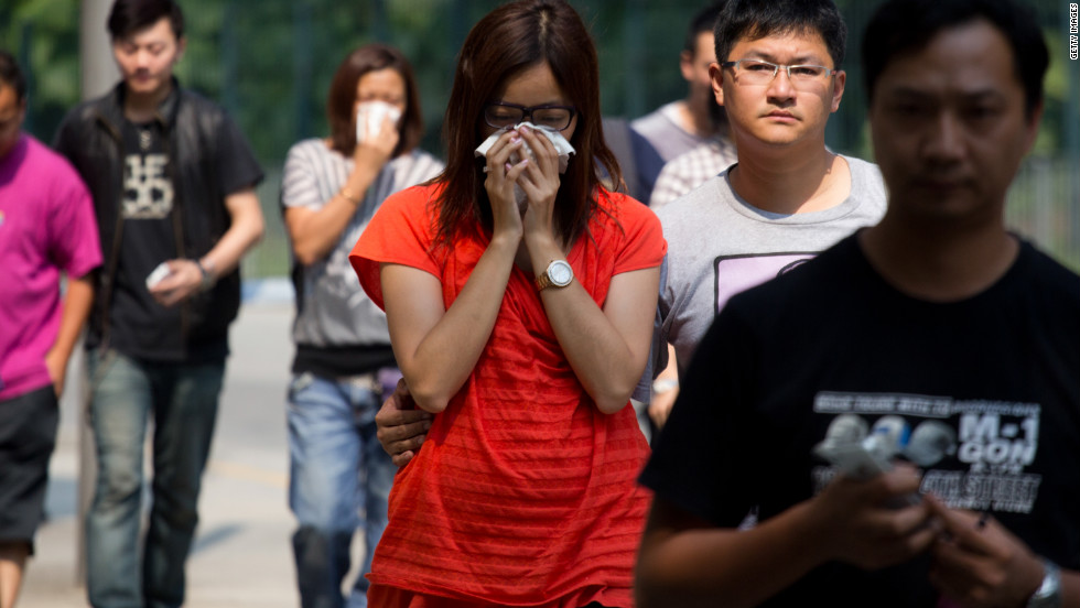 A woman cries Tuesday as she leaves a public mortuary holding the bodies of those who died in the boat collision.