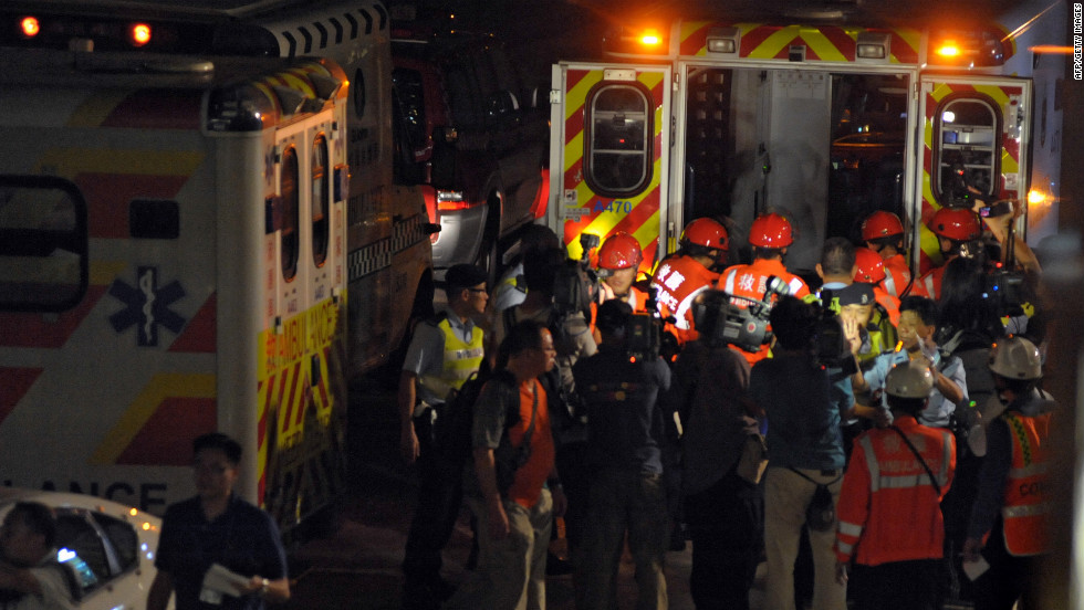 Members of the media surround rescue workers as they carry a victim into an ambulance Monday night.