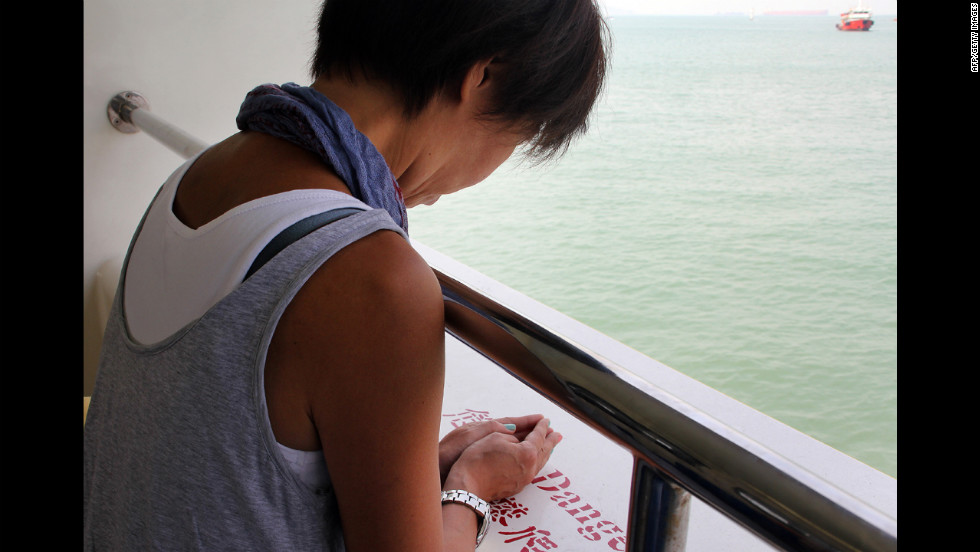 A woman offers a prayer on board a ferry off Hong Kong on Wednesday.