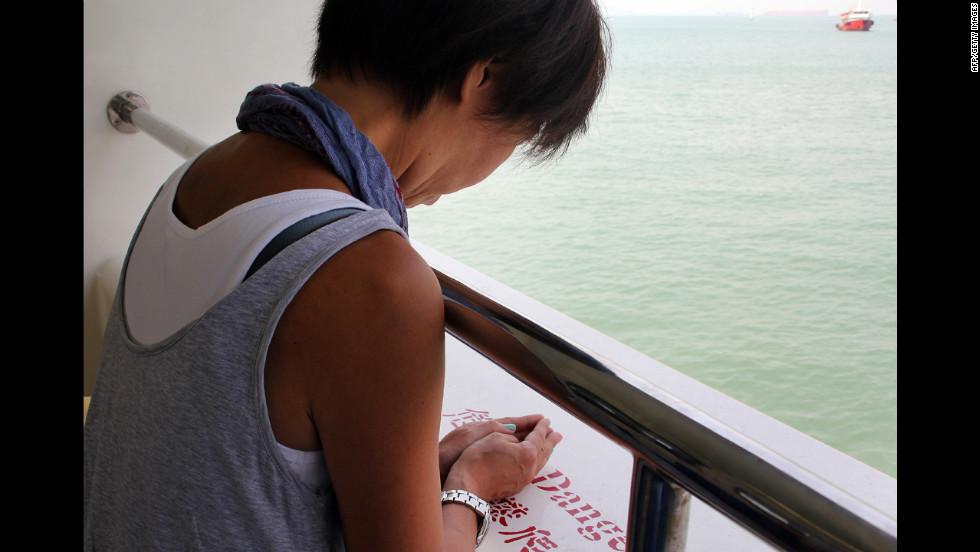A woman offers a prayer on board a ferry off Hong Kong on Wednesday.