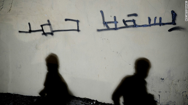"Shadows of Bahraini Shiites are seen on a wall with the Arabic writing ""Down with Hamad"" west of Manama on September 26."