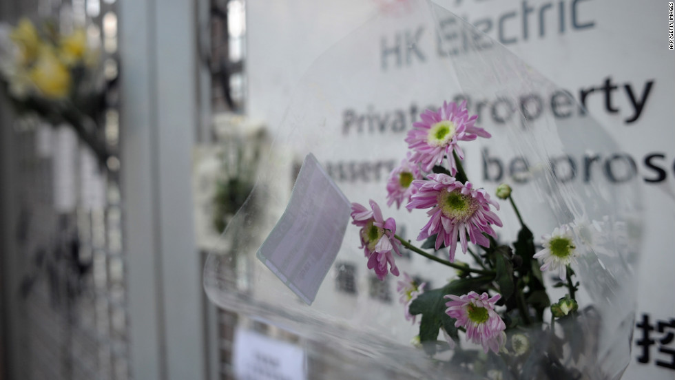 Bouquets of flowers and black ribbons hang on the gate to the HK Electric private pier on Thursday.