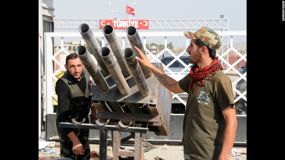 Syrian rebel fighters look at a multirocket launcher in Tal Abyadh, a Syrian town close to the Turkish border, on Thursday.
