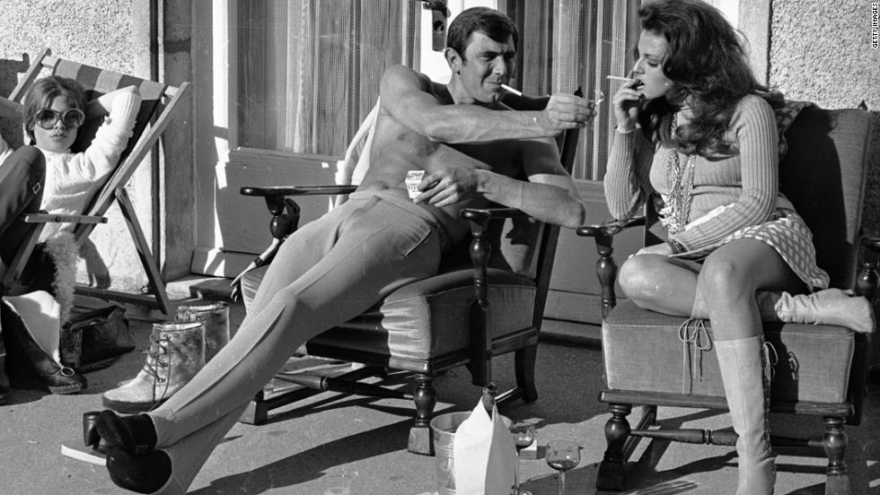 "George Lazenby offers co-star Helena Ronee a light during the filming of ""'On Her Majesty's Secret Service"" in the Swiss Alps in October 1968."