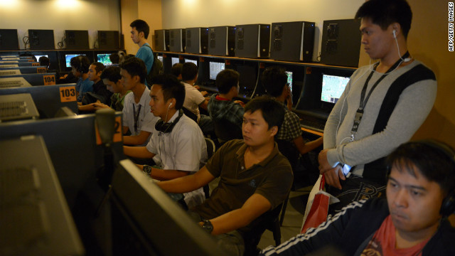 Customers at an Internet cafe look at Facebook profiles that have turned black as part of a protest against new cyberlaws.