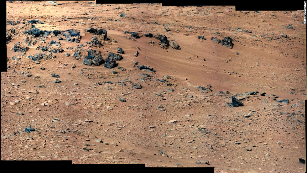 An area of windblown sand and dust downhill from a cluster of dark rocks has been selected as the likely location for the first use of the scoop on the arm of NASA's Mars rover Curiosity.