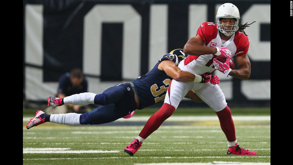 Larry Fitzgerald of the Arizona Cardinals attempts to break a tackle by Cortland Finneganof the St. Louis Rams.