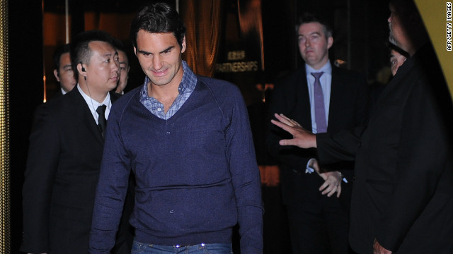 Roger Federer is flanked by security guard as he arrives for the ceremonial draw for the Shanghai Masters in China.