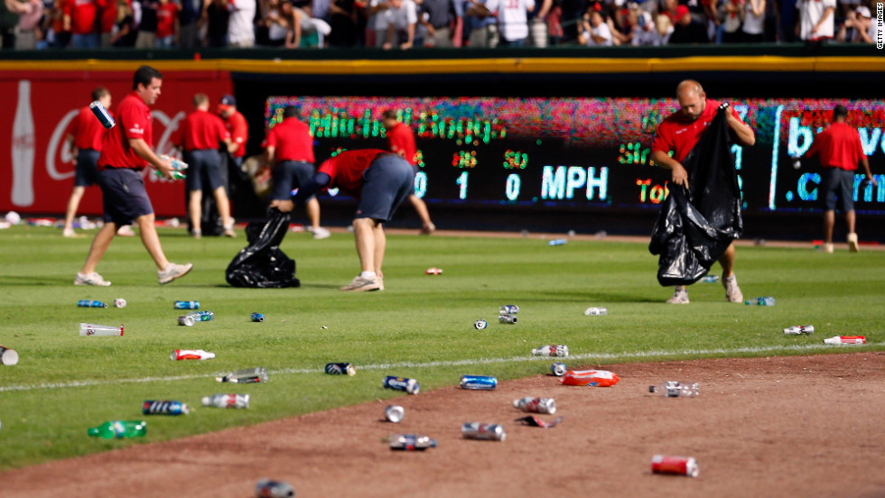 The grounds crew cleans up bottles and cups thrown by fans.