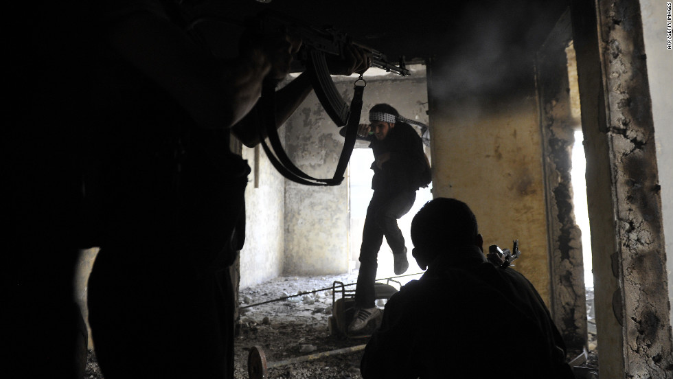 Syrian rebels take up positions inside a building during clashes with government forces in Aleppo on Saturday, October 6.