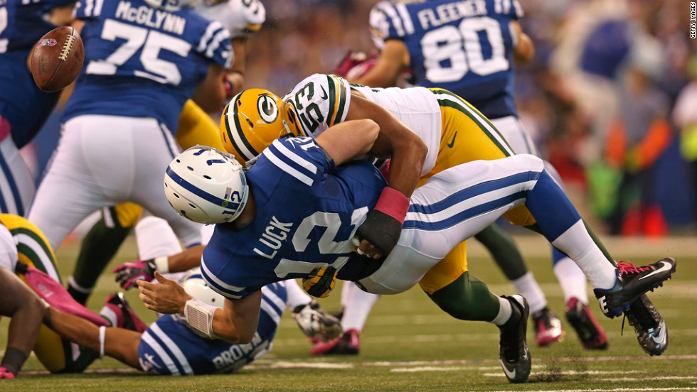 Andrew Luck of the Indianapolis Colts loses the ball as he is hit by Nick Perry of the Green Bay Packers.