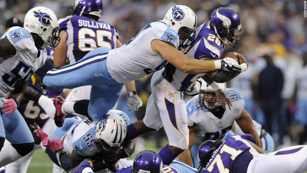 Karl Klug of the Tennessee Titans tackles Adrian Peterson of the Minnesota Vikings in the second quarter on Sunday.
