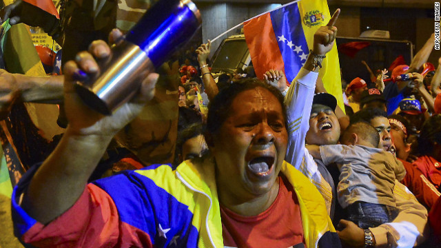 Venezuelan President Hugo Chavez (C-on balcony) speaks to supporters after receiving news of his reelection in Caracas on October 7, 2012. According to the National Electoral Council, Chavez was reelected with 54.42% of the votes, beating opposition candidate Henrique Capriles, who obtained 44.97%. AFP PHOTO/Luis Acosta        (Photo credit should read LUIS ACOSTA/AFP/GettyImages)