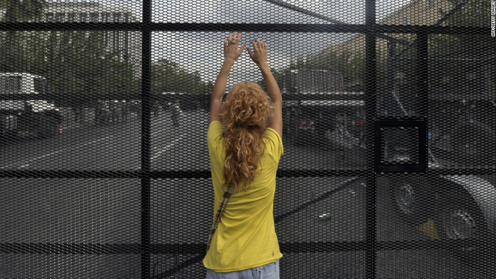 A protester stands against a barrier erected to protect the Greek parliament.