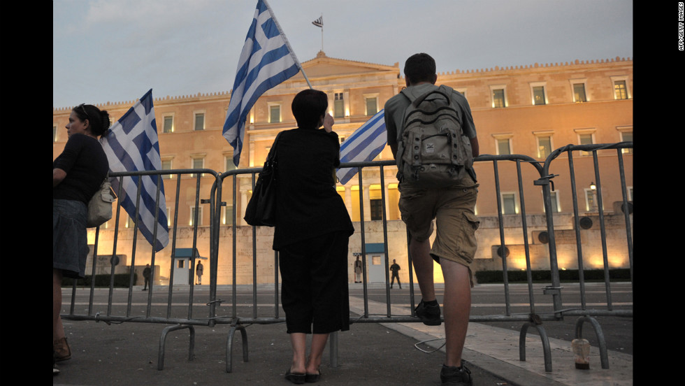 Protesters hold Greek flags behind barriers in front of the Greek Parliament.