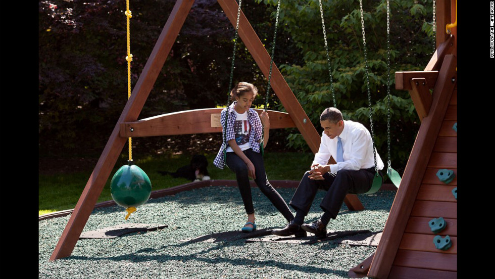 Obama talks with his daughter Malia on the swingset outside the Oval Office on May 4, 2010.