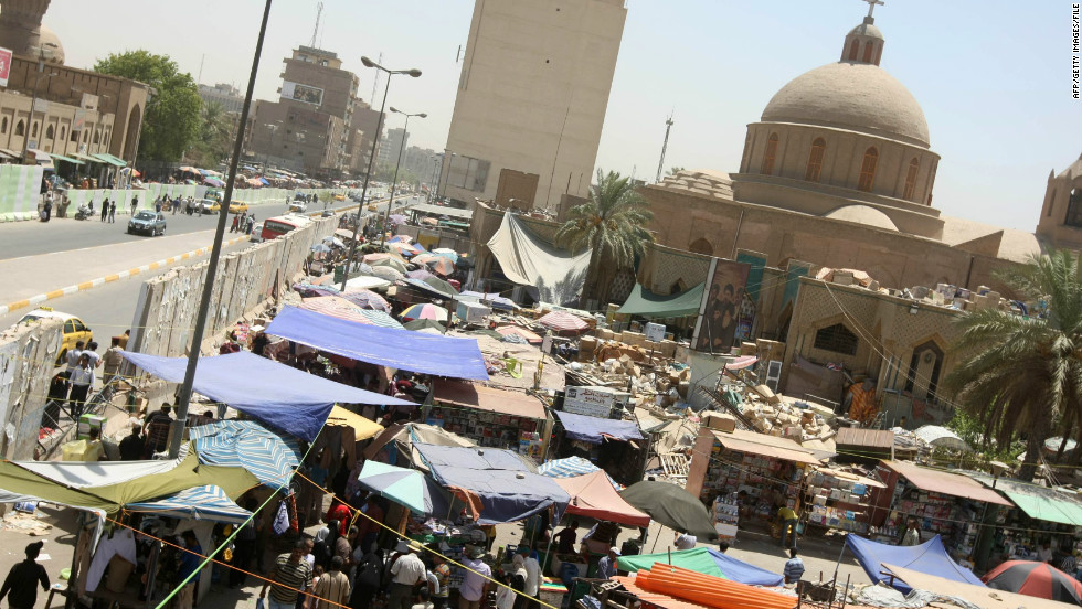 Markets in Baghdad (this one in 2010) are sometimes held in the shadows of blast walls in an effort to prevent suicide car bombings.