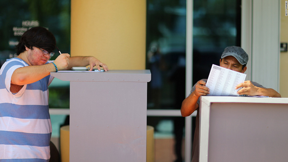 Allan Banojakedjian, left, and Jesus Romero fill out their voter registration forms at the Miami-Dade Elections Department on the final day of registration for the upcoming presidential election.