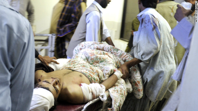 Pakistani relatives carry an injured blast victim at a hospital in Quetta on October 11, 2012.