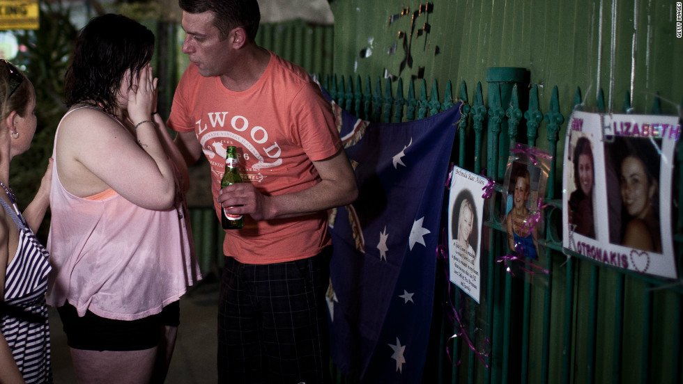A grieving relative is comforted at the bomb site in Bali, October 10, 2012. Wreaths, flowers and photos are being left at the site as a temporary shrine to those killed.