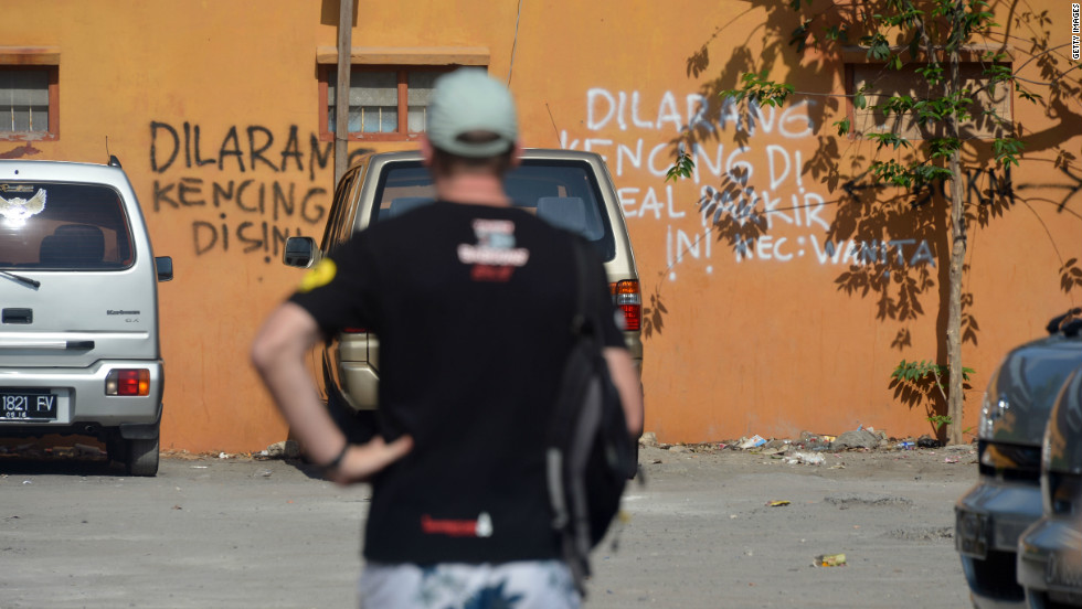 "Words spray-painted on the side of a wall near the Sari Club bomb site read in Indonesian ""don't urinate here."" Campaigners are fighting for a permanent memorial to be build on the site, a peace park to allow for quiet reflection, but negotiations have been delayed over price."