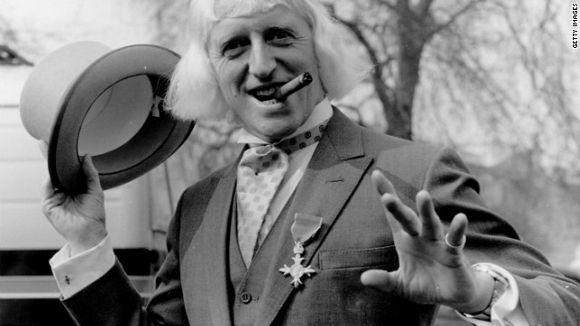 1972: British radio disc jockey, television broadcaster and charity fundraiser Sir Jimmy Savile sporting his OBE after his investiture at Buckingham Palace, London. (Photo by Fox Photos/Getty Images)