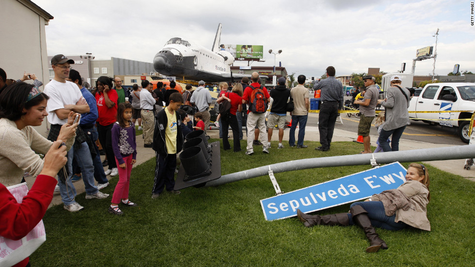 People pose with a street sign that was removed to make way for the space shuttle Endeavour during its transport from LAX to the California Science Center.