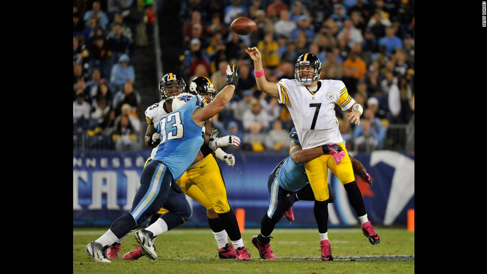 Roethlisberger, the Steelers quarterback, throws a pass while in a Titan's grasp.