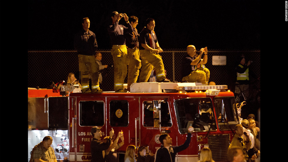 Firefighters and other spectators document the move early Friday.