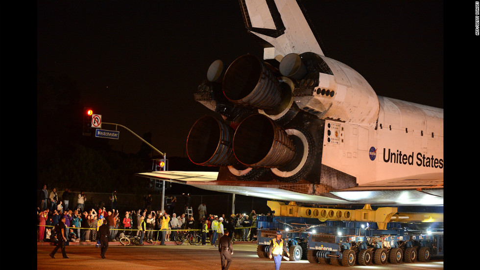 Bystanders watch as Endeavour moves out of the Los Angeles airport and onto a public street.