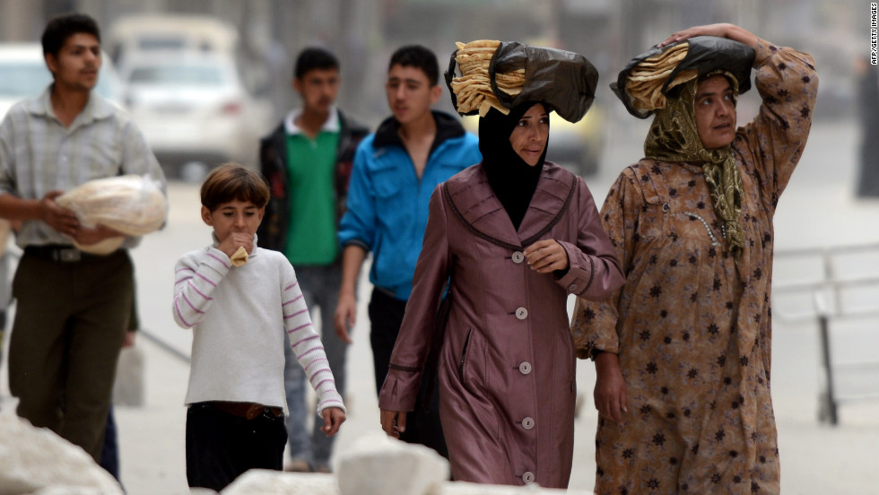 Syrian people carry bread as they walk in the streets of Aleppo on Thursday.