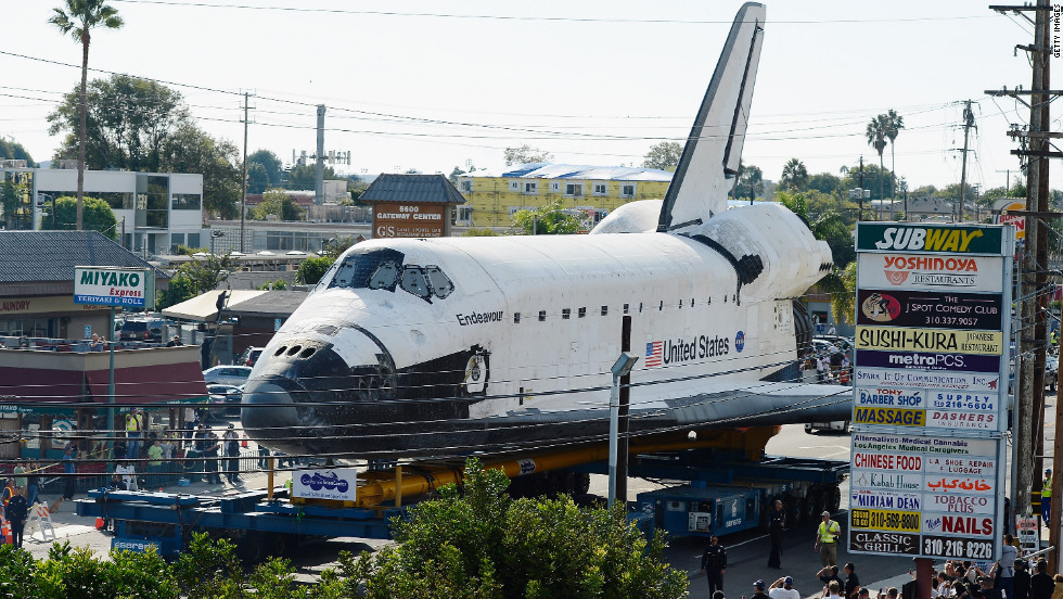 Endeavour makes its way past restaurants and shopping centers in Los Angeles.