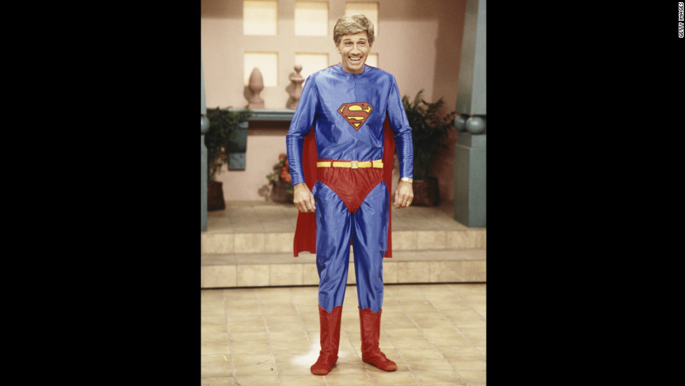 "Collins poses in a Superman costume during the taping of ""Hour Magazine"" in 1987 in West Hollywood, California."
