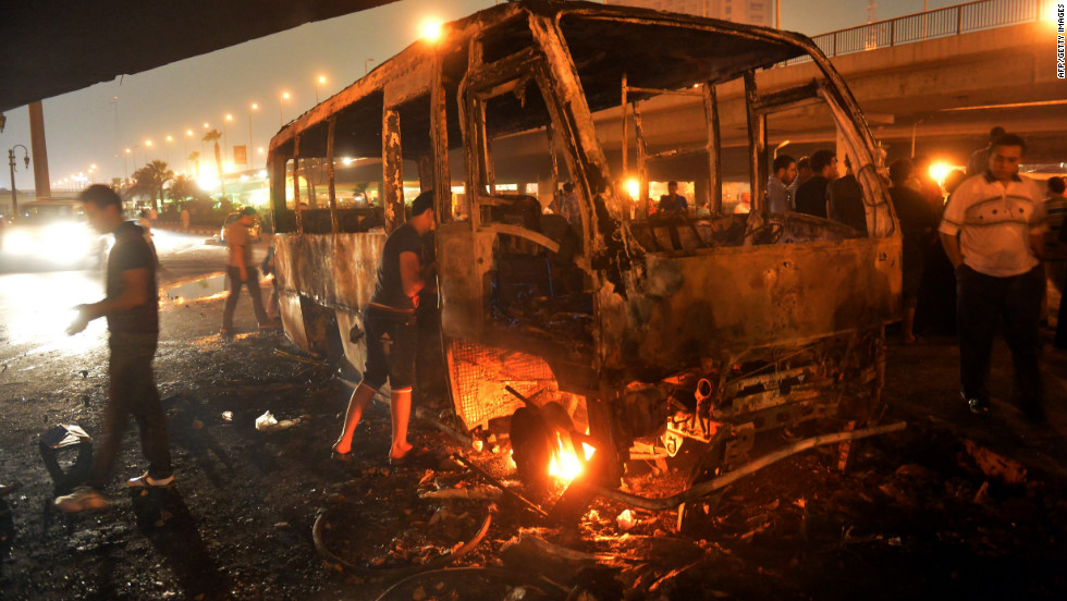 Egyptians inspect a bus that was set on fire during clashes between government supporters and opponents of the Muslim Brotherhood and President Mohamed Morsy.