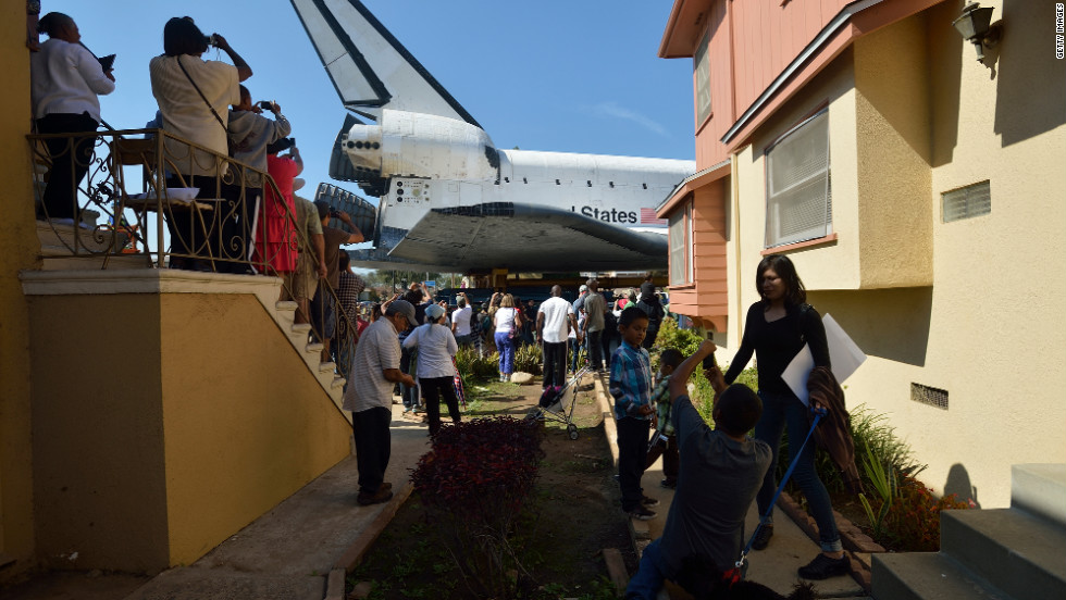People watch Endeavour pass residential buildings on Crenshaw Drive. Over two days, the 170,000-pound shuttle will travel at no more than 2 mph along a 12-mile route from Los Angeles International Airport to its final home.