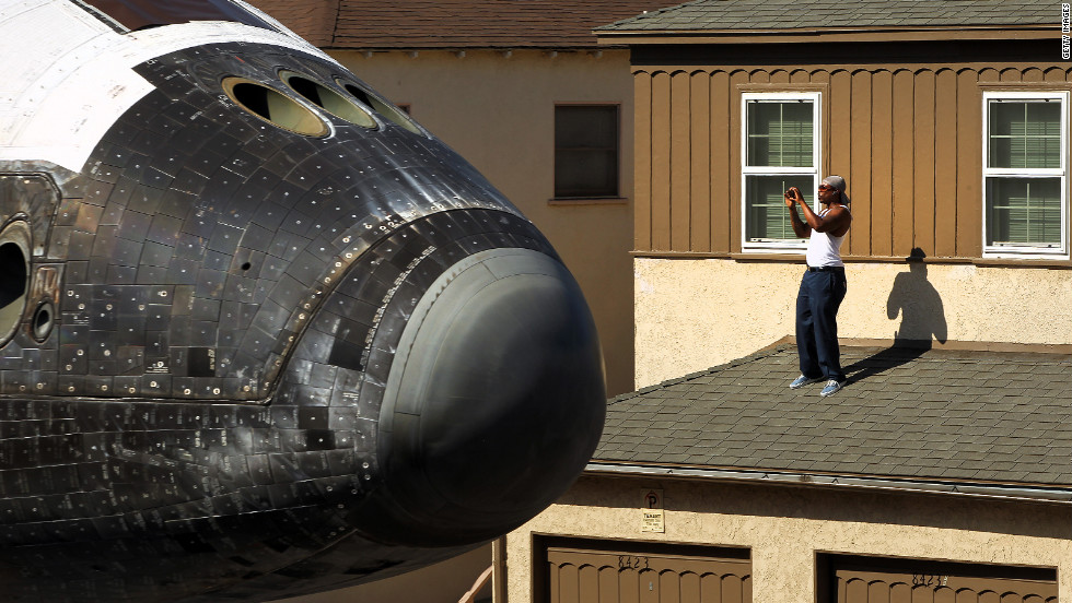A man takes a picture from a rooftop as Endeavour makes its way toward the California Science Center on Saturday.