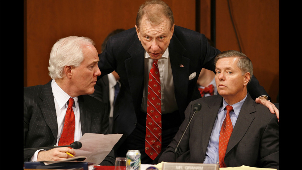 From left, Sen. John Cornyn of Texas, Specter and Sen. Lindsey Graham of South Carolina confer while U.S. Attorney General Alberto Gonzales testifies during a hearing in February 2006 in Washington.
