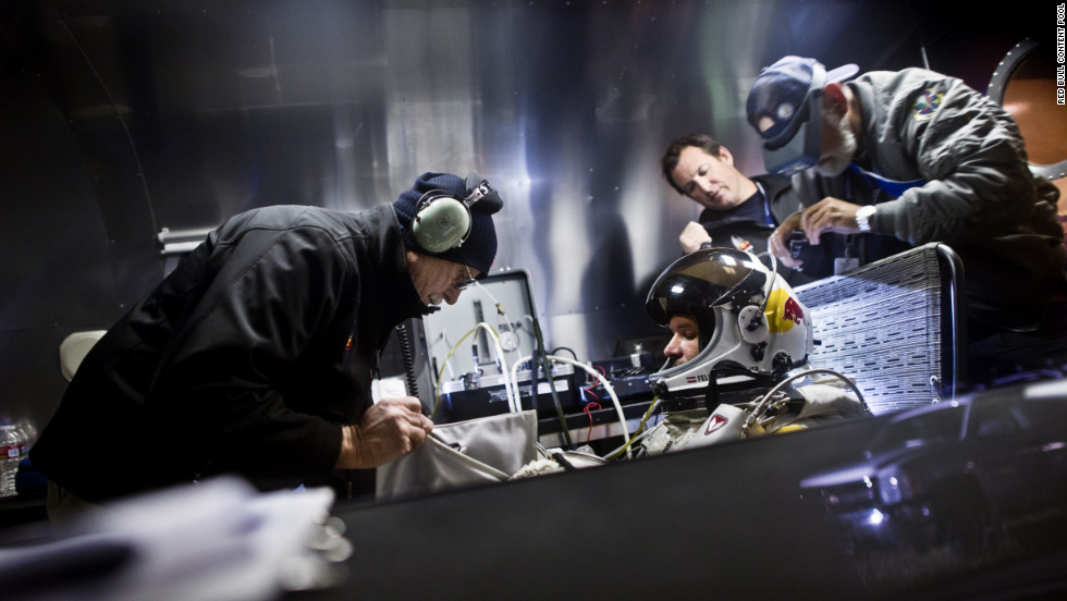 Crew members assist Baumgartner in his trailer. The Red Bull Stratos team includes a former NASA crew surgeon, record-breaking aviators and innovative aircraft designers.
