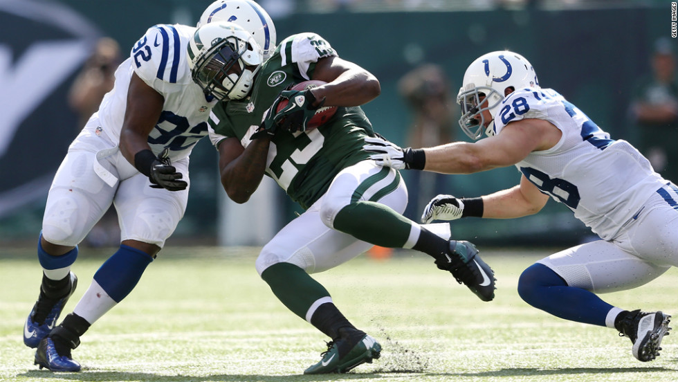 Shonn Greene of the Jets is tackled by Jerry Hughes, left, and Tom Zbikowski of the Colts on Sunday.