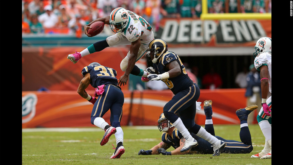 Reggie Bush of the Miami Dolphins jumps over No. 31 Cortland Finnegan of the St. Louis Rams on Sunday at Sun Life Stadium in Miami Gardens, Florida.