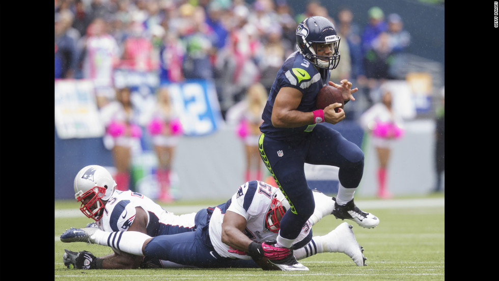 Russell Wilson of the Seattle Seahawks escapes the grasp of the Patriots' Jerod Mayo.